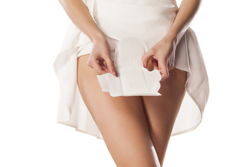 A woman holds a sanitary pad over her crotch