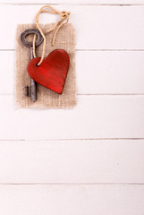 Old  key with a heart on white vertical