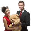smiling elegant couple holding big soft toy