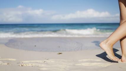 close up of woman legs walking on beach