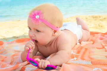 Little girl holding sunglasses on the sea shore
