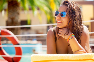 beautiful young woman with sunglasses relaxing by the pool