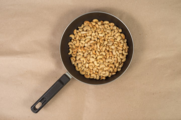 Roasted cashews in frying pan on paper