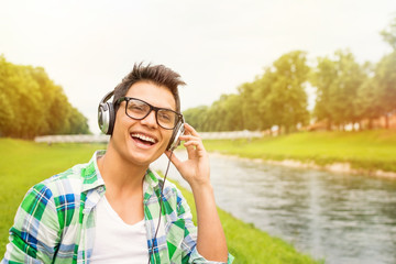 Hipster young man with headphones outdoors
