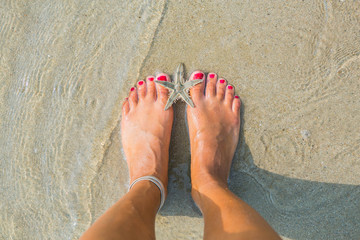 Human feet on sand with a starfish