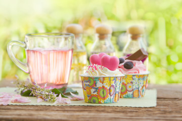Rose tea  and sweet cupcake on table in the garden