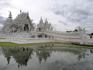 Wat Rong Khun under cloudy sky with reflection