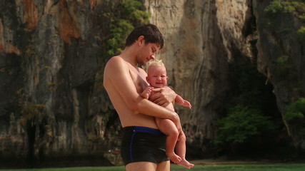 brunette man holding a crying baby