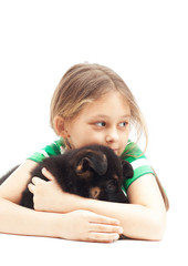 child  gently hugs puppy on white background