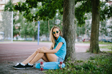 beautiful girl sitting near the skateboard