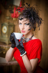 Fashionable attractive young woman in red dress drinking coffee