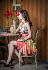 Fashionable attractive woman in multicolored dress sitting