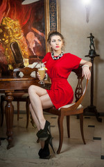 Fashionable attractive young woman in red dress with latte