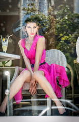 Fashionable attractive young woman in pink dress sitting