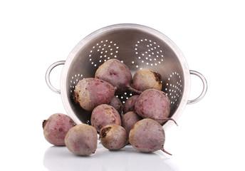 Metal colander full of ripe beets.