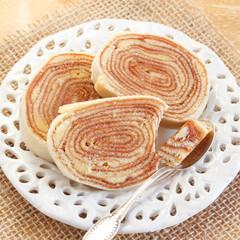 Brazilian dessert Bolo de rolo (swiss roll, roll cake) on white