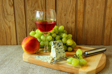 Still-life with a glass of rose wine, cheese and fruit.