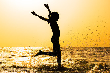 Silhouette of a girl running in the sea at sunset