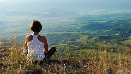 Young woman meditated on mountain top