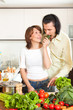 Brunette housewife with man cooking with fresh vegetables at hom