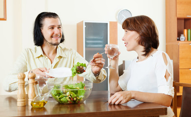 couple eating vegetarian salad with water