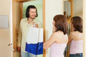 man gives gift to woman at home