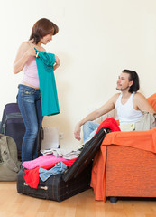 couple together with luggage leaving the home
