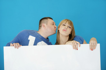 Sweet Young Couple Kissing Behind White Cover