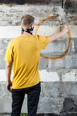 Young hooligan drawing a graffiti