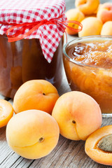 ripe apricot fruits and jar of jam on table