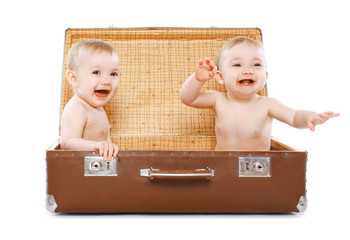 Two cheerful twins sitting in a suitcase having fun, travel, fam