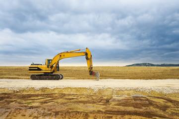 Bagger in weiter Landschaft auf Baustelle