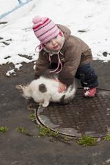 Ребёнок пытается поднять кота