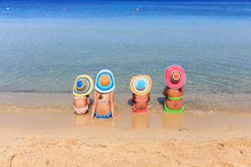 Girls with colorful hats on the beach