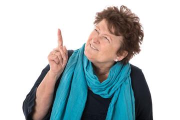 Witzige rüstige Seniorin zeigt mit dem Zeigefinger