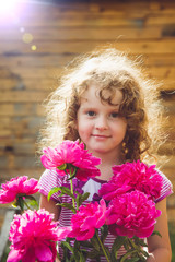 Curly baby with flowers in her hand. Toning photo. Instagram fil