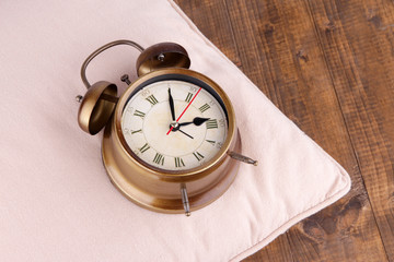 Metal clock on a pink pillow on wooden background
