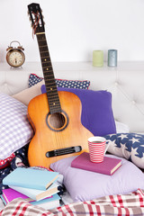 Guitar on pillows on a bed on white background