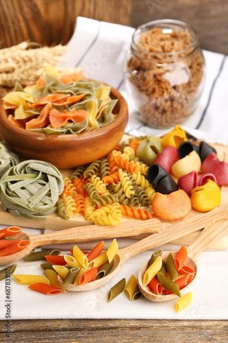 Leinwandbild Motiv Variety of colorful pasta on wooden background