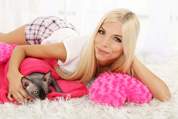 Beautiful young woman with gray sphinx cat lying