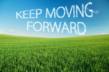 Keep moving forward written in clouds over green field