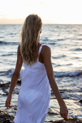 Woman in sundress relaxing at sea at sunset