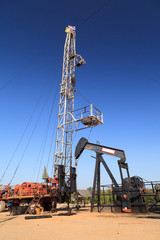 Oil Pump Jack (Sucker Rod Beam) and Workover Rig on Sunny Day