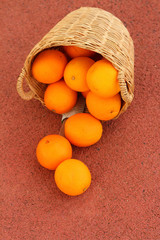 Basket of oranges on red background