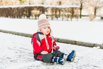 Cute toddler boy playing with the first snow
