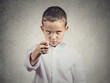 Upset boy giving figa gesture with hand, grey wall background