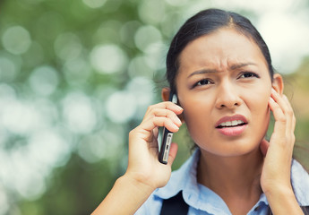 Unhappy, stressed woman talking on mobile phone outside