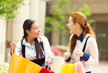 Happy shopper women showing new gifts they have purchased