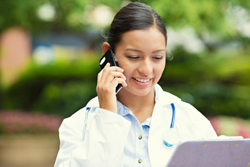 Happy doctor, female nurse talking on a phone, outside hospital