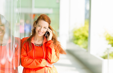 Happy woman talking on mobile phone outside city background